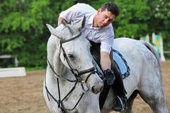 Jockey seat on horse feed from hand Royalty Free Stock Image