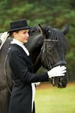 Jockey in uniform with horse. Horsewoman in uniform standing with horse outdoors Stock Photography