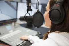 Jockey Wearing Headphones While Using Microphone In Radio Studio. Young female jockey wearing headphones while using microphone in radio studio royalty free stock photos