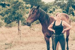 Jockey woman walking with horse on meadow Stock Images