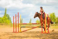 Jockey young girl doing horse jumping through hurdle. Taking care of animals, horsemanship, western competitions concept. Jockey young girl doing horse jumping stock photo
