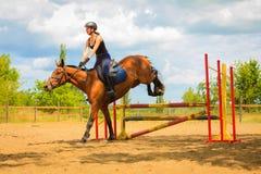 Jockey young girl doing horse jumping through hurdle stock images