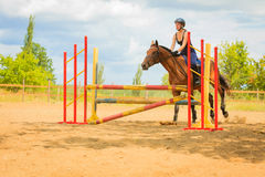 Jockey young girl doing horse jumping through hurdle Stock Photo