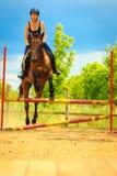 Jockey young girl doing horse jumping through hurdle Stock Photography