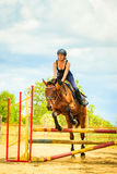 Jockey young girl doing horse jumping through hurdle. Taking care of animals, horsemanship, western competitions concept. Jockey young girl doing horse jumping royalty free stock images