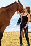 Jockey young girl kissing and hugging brown horse stock photo
