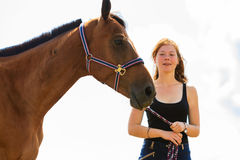 Jockey young girl petting brown horse. Taking care of animals, love and friendship concept. Jockey young girl petting brown horse on sunny day stock photo