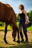 Jockey young girl petting brown horse. Taking care of animals, love and friendship concept. Jockey young girl petting brown horse on sunny day stock photography