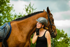 Jockey young girl petting and hugging brown horse Stock Photos