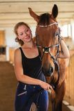 Jockey young girl petting and hugging brown horse stock photography
