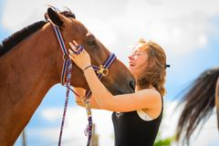 Jockey young girl petting and hugging brown horse Royalty Free Stock Image