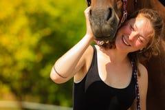 Jockey young girl petting and hugging brown horse stock image