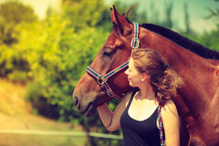 Jockey young girl petting and hugging brown horse. Taking care of animals, love and friendship concept. Jockey young girl petting and hugging brown horse on royalty free stock photography