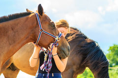 Jockey young girl petting and hugging brown horse. Taking care of animals, love and friendship concept. Jockey young girl petting and hugging brown horse on royalty free stock photos