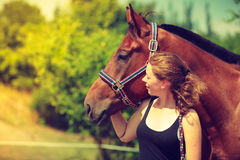 Jockey young girl petting and hugging brown horse Royalty Free Stock Photos