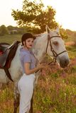 Jockey young girl petting and hugging white horse in evening sunset. Sun flare. Taking care of animals, love and friendship concept. Jockey young girl petting stock photo
