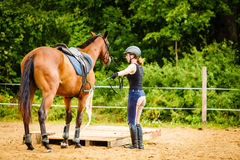 Jockey young woman getting horse ready for ride. Taking care of animals, horsemanship, equine concept. Jockey young woman in helmet getting horse ready for ride royalty free stock photo