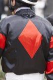 Jockeydetail vóór het ras Renbaanachtergrond renpaard Stock Foto