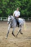 Jockeyen i exponeringsglas, den vita skjortan rider hästen Royaltyfri Fotografi
