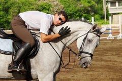 Jockeyen i exponeringsglas kramar hästen Royaltyfria Foton