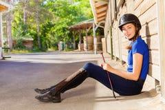 Jockeymädchen, das außerhalb eines Kastenstalls mit Peitsche sitzt Lizenzfreies Stockfoto