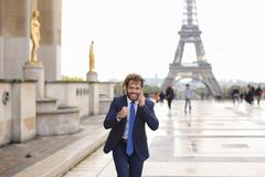 Jocund guy raving near Eiffel Tower and calling friend b. Happy young boy having fun and talking with friend with smartphone near Eiffel Tower in background Royalty Free Stock Image