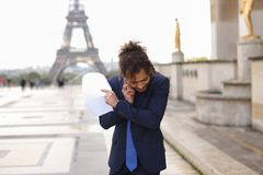 Jocund guy raving near Eiffel Tower and calling friend b. Happy young boy having fun and talking with friend with smartphone near Eiffel Tower in background Stock Images