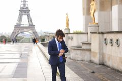 Jocund mulatto guy raving near Eiffel Tower and calling friend b. Happy young boy having fun and talking with friend with smartphone near Eiffel Tower in Royalty Free Stock Image