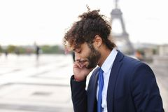 Jocund mulatto guy raving near Eiffel Tower and calling friend b. Happy young boy having fun and talking with friend with smartphone near Eiffel Tower in Royalty Free Stock Images