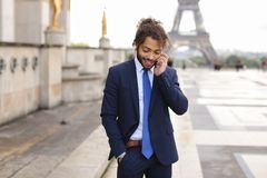 Jocund mulatto guy raving near Eiffel Tower and calling friend b. Happy young boy having fun and talking with friend with smartphone near Eiffel Tower in Stock Photography