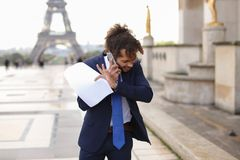 Jocund mulatto guy raving near Eiffel Tower and calling friend b. Happy young boy having fun and talking with friend with smartphone near Eiffel Tower in Royalty Free Stock Photo