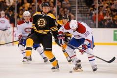 Joe Corvo and Travis Moen. Boston Bruins defenseman Joe Corvo and Canadiens forward Travis Moen battle for the puck Royalty Free Stock Image