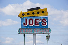 Joe does crabs. A Joe's Crab Shack sign against a backdrop of clouds Stock Photos