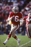 Joe Montana of the San Francisco 49ers. Joe Montana dropping back in the pocket  to pass the Football at a NFL Game Stock Photos