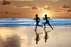 Jog. Woman and men running during sunset Stock Photo