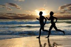 Jog. Woman and men running during sunset Stock Photos