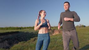Jog outdoors, happy young athletic couple enjoying jog in nature and cuddling in sunny daylight after cardio workout stock footage