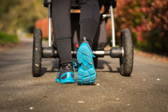 Jog in a park. Young mother exercises in a park. Wears blue-gray sport shoes, pushes a pram Stock Image