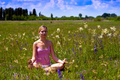Joga. Beautiful young woman relaxing on the field Stock Images