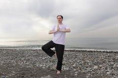 joga czyni człowieka na plaży Obraz Stock