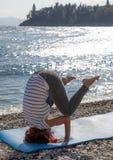 Joga de ejecución de la mujer en costa de mar Foto de archivo