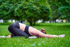 Joga dziecka poza - Balasana Młodej kobiety joga ćwiczy medytacja w naturze przy parkiem Zdrowie stylu życia pojęcie obrazy stock