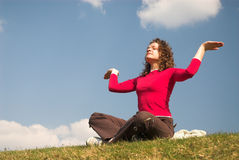 Joga-girl. Pretty female is siiting and meditating on sky backlgroung royalty free stock photos