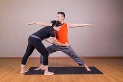 Joga instruktor koryguje studenckiego spełnianie wojownika 2 lub Virab Zdjęcie Stock