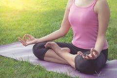 Joga kobieta medytuje w lotosie pozuje przy parkiem Obraz Stock