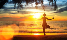 Joga kobieta na dennym wybrzeżu przy zmierzchem medytacja Zdjęcia Stock