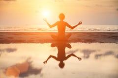 Joga kobiety obsiadanie w lotos pozie na plaży podczas zmierzchu Fotografia Royalty Free