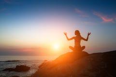 Joga medytaci kobiety sylwetka na morzu podczas zadziwiającego zmierzchu Obrazy Stock