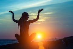 Joga medytaci sylwetka Sprawności fizycznej kobieta na oceanie podczas zadziwiającego zmierzchu Fotografia Stock