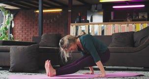 Joga medytacja dla blondynki kobiety jest ubranym wygodnego sportswear i ćwiczy joga w żywym pokoju w domu zbiory wideo